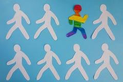 Der Papiermann, der in den Farben der LGBT-Flagge gemalt wird, läuft aus der grauen Masse heraus lizenzfreie stockfotos