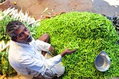 Der Paprikaverkäufer, der Geschäft in einem asiatischen Gemüsemarkt tätigt Stockfotografie