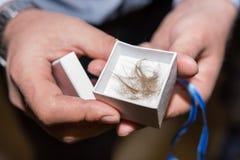 Der Pate hält wenig Kasten mit dem geschnittenen Haar während der Tauftaufezeremonie an der Kirche stockbilder