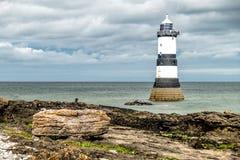 Der Penmon-Punktleuchtturm ist nah an Papageientaucher-Insel auf Anglesey, Wales - Vereinigtes Königreich Stockfotografie