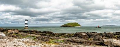 Der Penmon-Punktleuchtturm ist nah an Papageientaucher-Insel auf Anglesey, Wales - Vereinigtes Königreich Stockfotos