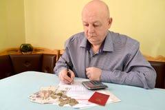 Der Pensionär betrachtet Barausgaben auf Gebrauchszahlungen lizenzfreie stockbilder