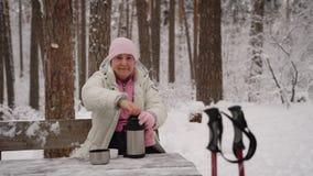 Der Pensionär im Winterholz Die ältere Frau sitzt auf einer Bank hat Rest und wird heißen Tee von der Thermosflasche trinken stock footage