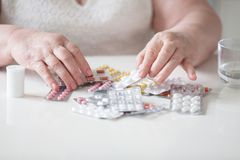 Der Pensionär nimmt seine Pillen mit seinen Händen ein stockbild