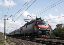 Der Personenzug mit der elektrischen Lokomotive Lizenzfreie Stockfotos