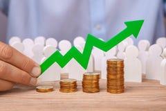 Der Pfeil des Diagramms ist aufwärts, Mann und Stapel der Münzentreppe halten Umsatzwachstum, Gewinne, Investitionen Stockfoto