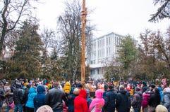 Der Pfostenaufstieg auf dem glatten hölzernen Pfosten auf Maslenitsa, Leute feiern Feiertag in Moskau Lizenzfreies Stockbild