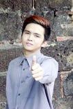 Der philippinische Mann machend Daumen up Zeichen stockfotografie