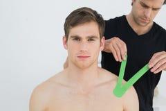 Der Physiotherapeut, der auf kinesio Band auf Patienten sich setzt, schultern Stockbild