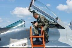 Der Pilot und der Besucher nahe dem Cockpit des multirole Kämpfers Mikojan-Gurewitsch MiG-29 lizenzfreies stockbild