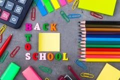 Der Plan des Schulbedarfs auf einem dunkelgrauen Hintergrund Die Ansicht von der Oberseite Flache Lage Zur?ck zu Schule stockbilder