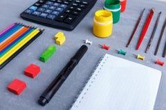 Der Plan eines Notizbuches, der farbigen Bleistifte, des Taschenrechners und der Farben mit Bürsten Lizenzfreies Stockfoto