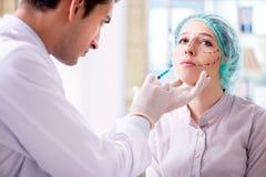 Der plastische Chirurg, der für Operation auf Frauengesicht sich vorbereitet lizenzfreie stockbilder