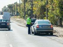 Der Polizist überprüft Dokumente vom Fahrer des Autos auf dem Intercityweg am Eingang zu Bukarest-Stadt in Rumänien Stockfotografie