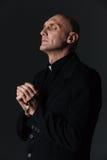 Der Priester, der Rosenbeet hält und mit Augen betet, schloss lizenzfreie stockfotos