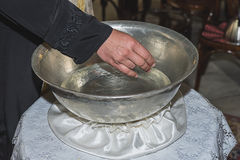 Der Priester segnet das Tauftaufbecken, das mit Weihwasser an der Kirche während der Zeremonie gefüllt wird Lizenzfreie Stockbilder