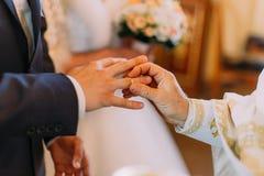 Der Priester setzt auf den Bräutigam den goldenen Ehering lizenzfreie stockbilder
