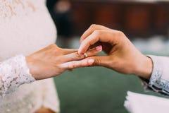Der Priester setzt den Ehering auf den Finger der Braut stockbilder