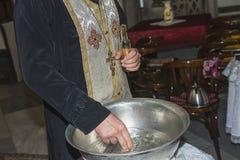 Der Priesterassistent füllte Tauftaufbecken mit Weihwasser an der Kirche während der Zeremonie stockfotografie