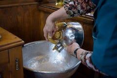 Der Priesterassistent füllte Tauftaufbecken mit Weihwasser an der Kirche während der Zeremonie Stockbild