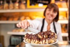 Der professionelle weibliche Bäcker ist Verkauf gebacken Lizenzfreie Stockbilder
