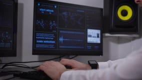 Der Programmierer gibt Informationen in eine Computerklasse ein Der Mann in einem hellen Hemd und in den Punkten versucht mittels stock footage
