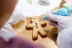 Der Prozess der Herstellung Sandmännchen der Plätzchen wenden manuell die Glasur Ihres children& x27 an; s-Hände Stockfoto