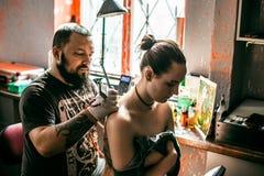 Der Prozess der Schaffung einer Tätowierung auf der Rückseite eines Mädchens Stockfotos
