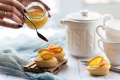 Der Prozess der Verzierung von kleinen Kuchen mit Orangenmarmelade Lizenzfreies Stockfoto