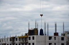 Der Prozess des Baus Baumaterialien werden an ein mehrstöckiges Gebäude im Bau unter Verwendung eines anhebenden cran geliefert lizenzfreie stockfotografie