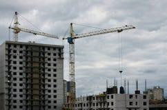 Der Prozess des Baus Baumaterialien werden an ein mehrstöckiges Gebäude im Bau unter Verwendung eines anhebenden cran geliefert lizenzfreies stockfoto