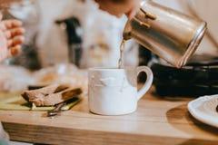 Der Prozess des Gießens des Kaffees von den Türken in eine schöne weiße Schale in der Küche auf einem Holztisch lizenzfreie stockfotos