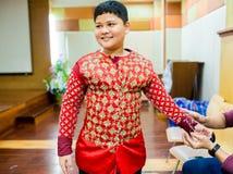 Der Prozess des Kleidens der thailändischen Pantomime für die Schauspieler mit der Hand nähend, reparierend lizenzfreie stockfotografie