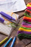 Der Prozess des Kreuzstichs Nadeln, Glasschlacke, Entwurf, Scheren, Bleistifte und Stift auf einem Holztisch Lizenzfreie Stockbilder