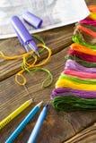 Der Prozess des Kreuzstichs Nadeln, Glasschlacke, Entwurf, Scheren, Bleistifte und Stift auf einem Holztisch Lizenzfreies Stockfoto