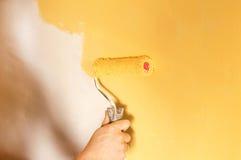 Der Prozess des Malens der Wände in der gelben Farbe Lizenzfreies Stockfoto