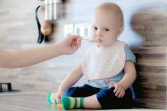Der Prozess der Fütterung des Babys mit Löffeln lizenzfreie stockfotos