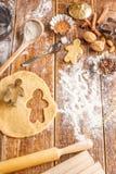 Der Prozess der Herstellung von klassischen Ingwerkeksen in Form von kleinen Männern Stillleben auf einem hölzernen Hintergrund m stockfotos