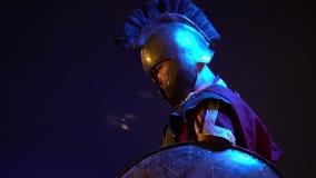 Der römische Gladiator in der ledernen Rüstung und im schweren Sturzhelm hält ein Schild und steht mit einem durchdachten Blick stock video footage
