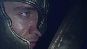 Der römische Gladiator in einem Sturzhelm und eine Narbe auf seinem Gesicht froren mit einer Klinge in seiner Hand ein, die oben  stock video