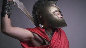 Der römische Legionär in seinem Sturzhelm und in roten Kittel verkratzt seins zurück mit seiner Klinge, Zeitlupe stock video