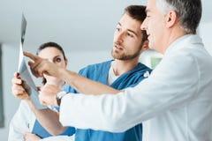 Der Röntgenstrahl des Untersuchungspatienten des Ärzteteams stockfotos