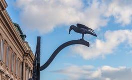 Der Rabe hält in seinem Schnabel einen Ring, das Corvin-Tor in Budapest, Ungarn stockfoto