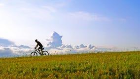 Der Radfahrer auf einer Wiese Lizenzfreie Stockfotografie