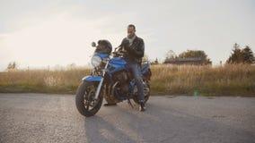 Der Radfahrer zieht Sturzhelm und Handschuhe aus und spricht am Telefon 4K stock footage