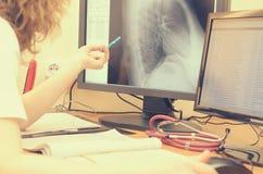 Der Radiologe betrachtet die Röntgenstrahlbilder auf einem Computermonitor Stockfotos