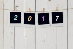 Der Rahmen mit vier Fotos und simsen 2017 für das neue Jahr, das am Weiß hängt, anflehen Stockfotos