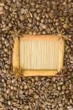 Der Rahmen wird vom Zimt, Sternanis, um den Kornröstkaffee auf der Hintergrundbambus Matte gemacht Ein Platz für Ihr inscr stockbilder