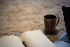 Der Rand einer einladenden offenen Zeitschrift mit Kaffeetasse und Laptop, lizenzfreies stockbild