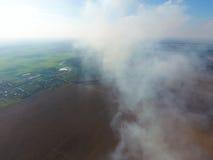 Der Rauch über dem Dorf Clubs des Rauches über dem Dorf bringt und Felder unter Aerophotographing-Bereiche Lizenzfreie Stockbilder